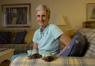 Carol Ann Ormes sitting on her couch with her two pet hermit crabs: Crab Kate and Jonathon Livingston Crab